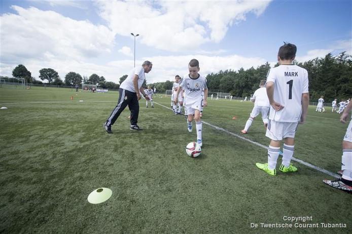 Beeld van de training van de Real Madrid Foundation met coördinator Frencis Malawau op het veld van Vroomshoopse Boys.