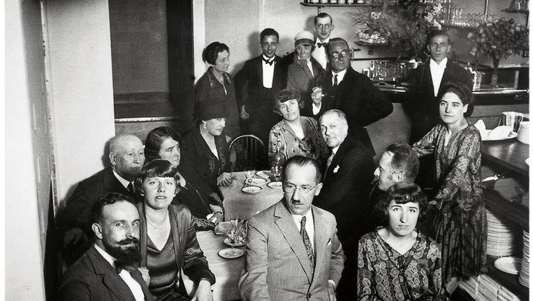 schilder Piet Mondriaan (midden, met bril) met een groep vrienden in een Parijs restaurant in 1926. Naast Mondriaan zit Vilmos Huszár (met baard en snor), achter hem staat onder anderen ontwerper Piet Zwart (met bril). Beeld Foto: Nederlands instituut voor Kunstgeschiedenis.