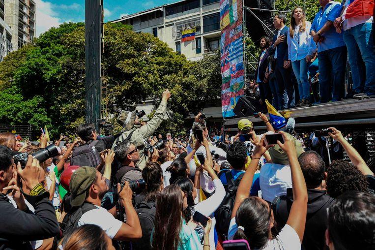 Demonstranten en pers verdringen zich voor het podium waar oppositieleider en zelfverklaard interimpresident Juan Guaidó met de hand op het hart klaar staat om een toespraak te houden. Beeld AFP