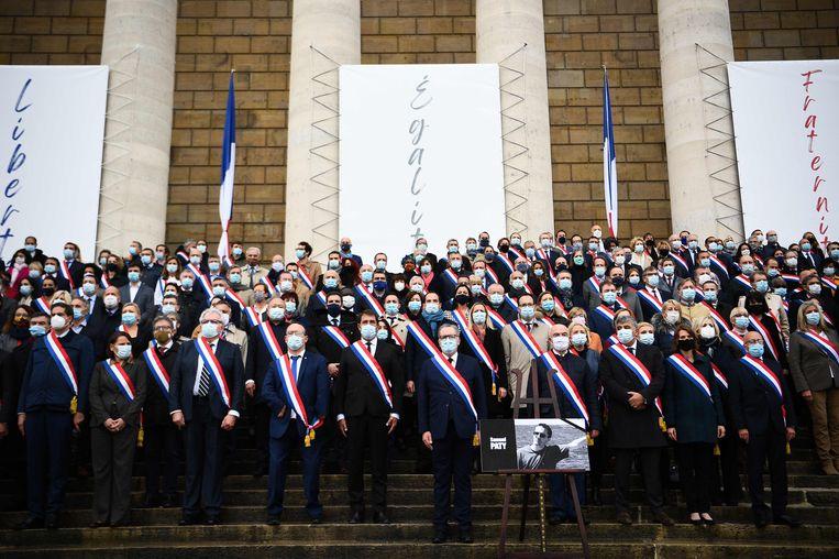 Franse parlementariërs betonen dinsdag hun eer aan de vermoorde leraar Samuel Paty voor het parlementsgebouw. Beeld AFP