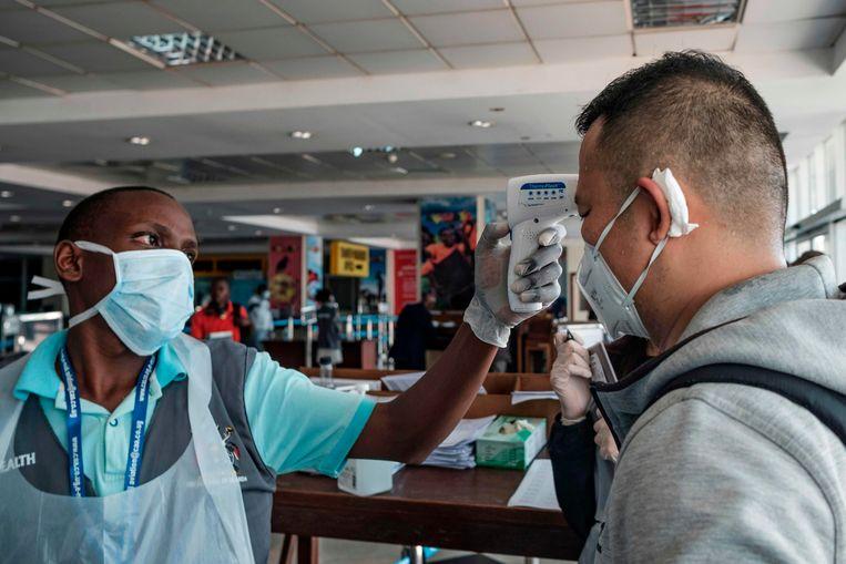 Een medewerker op het vliegveld van Entebbe in Oeganda checkt de temperatuur van een Chinese passagier.    Beeld AFP