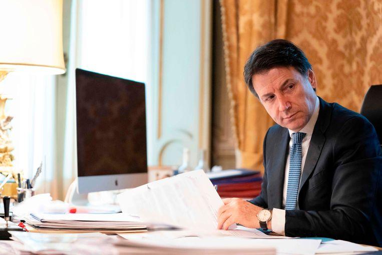 Italiaanse premier Giuseppe Conte in zijn kantoor. Beeld AFP
