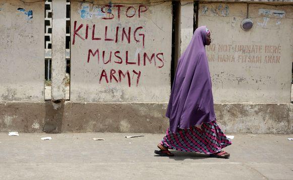Een moslimvrouw loopt in de Nigeriaanse stad Kano langs een opschrift dat het leger oproept te stoppen met het doden van moslims.