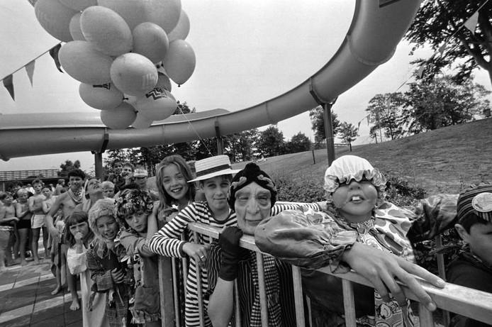 We hebben weer een foto waarop grote en kleine mensen verkleed zijn, nu uit 1985. Ze staan te trappelen om van de glijbaan te mogen.