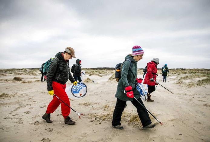 Vrijwilligers ruimen het strand van Terschelling op. Door de storm spoelt er waarschijnlijk komende dagen nog veel meer rotzooi aan.