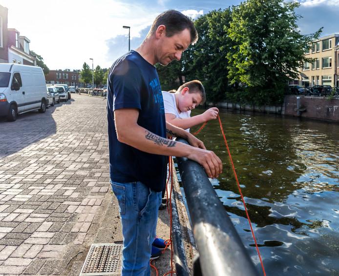 Vader Stefan en zoon Keano zijn aan het magneetvissen.