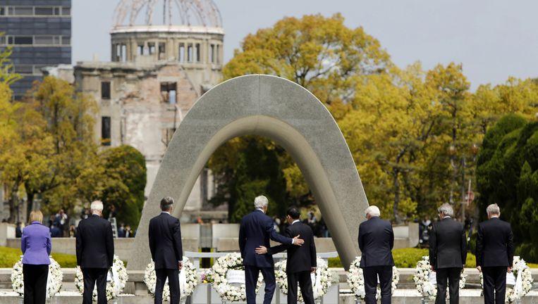 De G7-ministers leggen een krans bij het Hiroshima-monument in april. Kerry slaat zijn arm om zijn Japanse collega Beeld ap