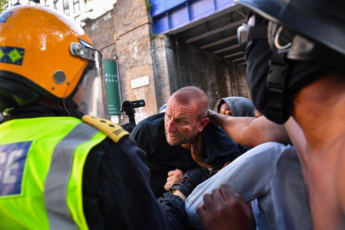 Zwarte demonstranten beschermen een tegen-demonstrant en dragen hem over aan de politie.