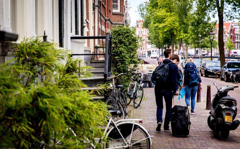 Toeristen in Amsterdam. De gemeente probeert illegale vakantieverhuur aan te pakken.  Beeld null