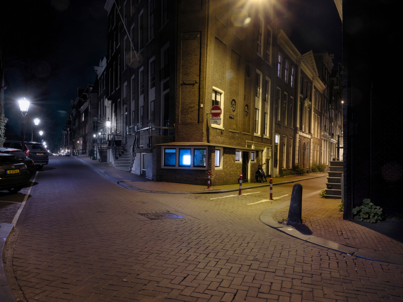 Amsterdam, leeg en verlaten door het coronavirus. Op de hoek van de Herengracht en de Beulstraat staat een eenzame voedselbezorger.