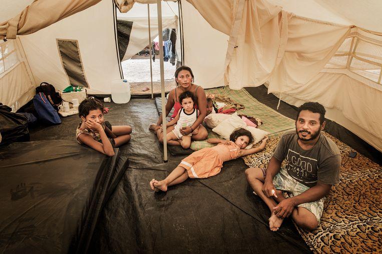 Migdalia Montier en Argenis Rodríguez met hun kinderen in een tentenkamp van de UNHCR in Colombia.   Beeld Mona van den Berg