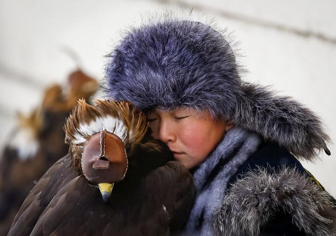 Een jonge Kazachstaanse jager knuffelt zijn steenarend tijdens de jaarlijkse wedstrijden waarbij de eeuwenoude technieken van deze jachtsport worden getoond. Foto Shamil Zhumatov