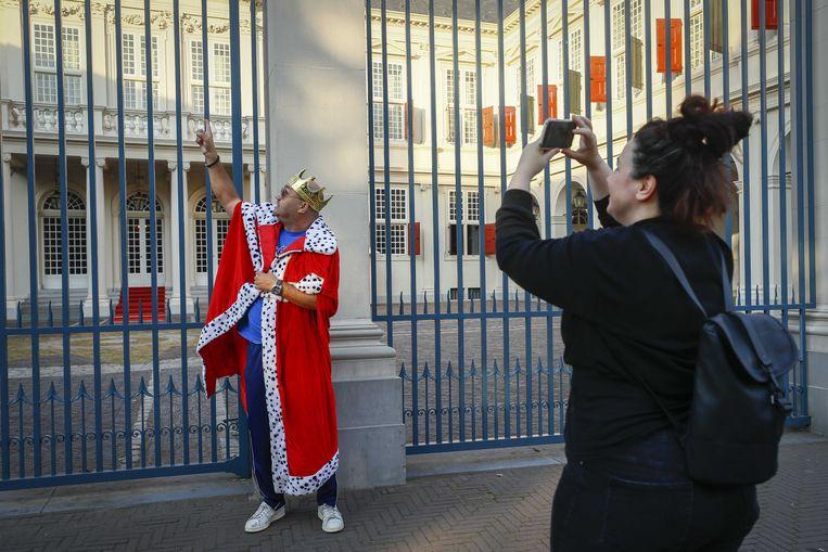 Vroege Oranjefans staan toch bij paleis Noordeinde in Den Haag. Vanwege de coronacrisis ziet Prinsjesdag er anders uit dan normaal. Beeld ANP