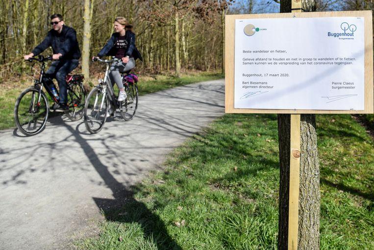 Aan de ingang van Buggenhout Bos wijst een infobord op de afstandsregels en het samenscholingsverbod.