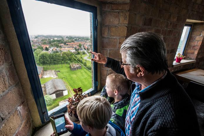 Gids Guus Langeraert weet (bijna) alles over Oostburg. Christijn (9) en Luca (8) kijken vanuit de watertoren mee.