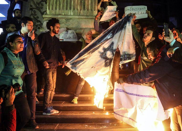 Demonstranten verbrandden woensdagavond de Israëlische vlag in de Egyptische hoofdstad Cairo.  Beeld EPA