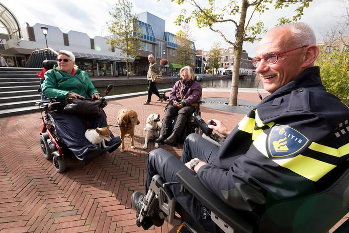 Wijkagent Coen van Stralen (rechts) ervaart hoe het is om in het centrum van Alphen aan den Rijn in een gemotoriseerde rolstoel te rijden.