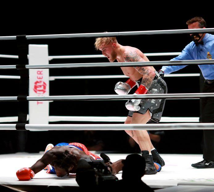 Jake Paul (midden) naast de voormalige NBA-speler Nate Robinson die knock-out op de mat ligt. Robinson werd uitgeschakeld tijdens de tweede ronde van hun bokswedstrijd op zaterdag 28 november 2020 in Los Angeles.