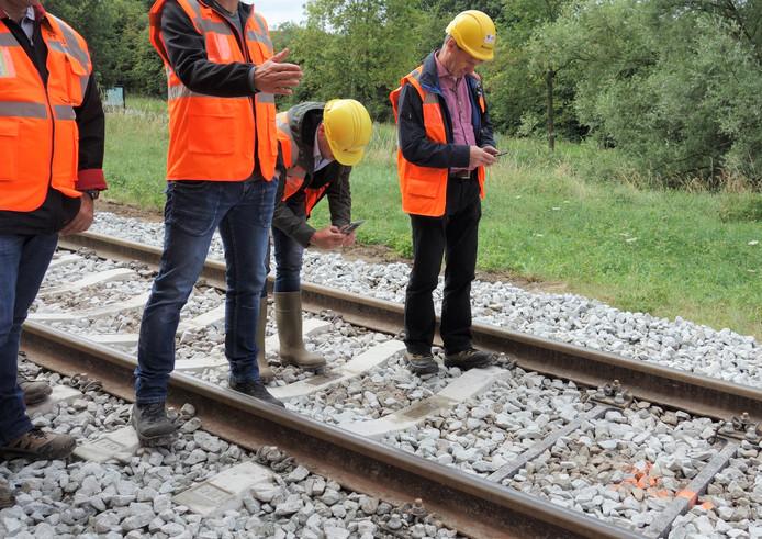 Uiterst rechts een van de nieuwe prototypes dwarsliggers. Medewerkers van ProRail en de producenten bekijken de verschillen op de baan tussen Zwolle en Heino.