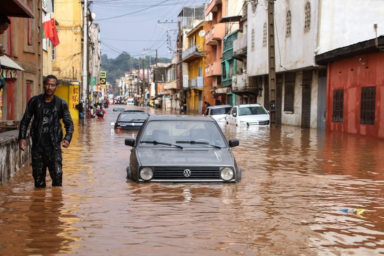 A resident walks through floodwaters past submerged vehicles on a road in Antananarivo on January 8, 2020, after heavy rainfall. (Photo by MAMYRAEL / AFP)