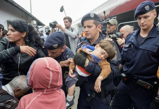 Oostenrijkse politieagenten helpen Syrische vluchtelingen op de trein naar Wenen.