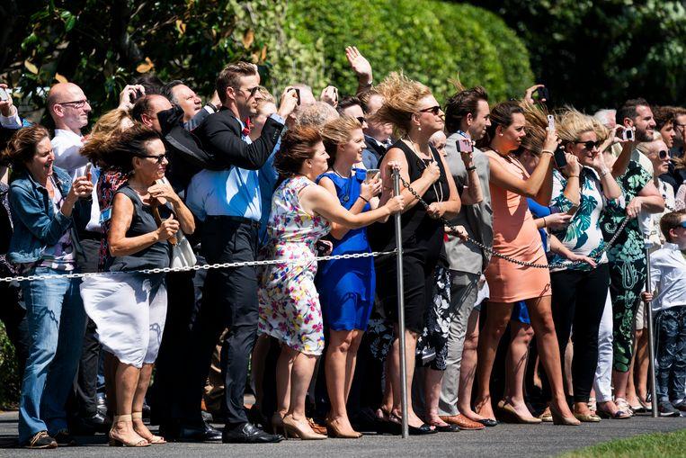 Mensen kijken toe hoe de Marine One – de helikopter van de Amerikaanse president – opstijgt. Beeld EPA