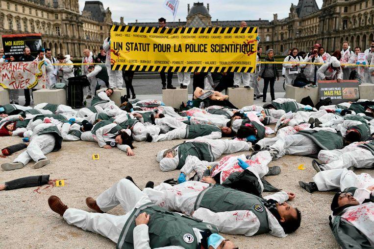 Forensische medewerkers van de politie hebben een 'plaats delict' ingericht in Parijs tijdens een demonstratie tegen de pensioenplannen. Zij moeten nu langer doorwerken dan gewone politie-agenten. Beeld AFP