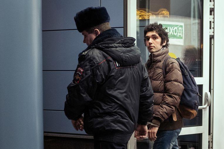 Arsjak Makitsjan (24)  wordt geboeid afgevoerd naar een Moskous detentiecentrum wegens het organiseren van een klimaatdemonstratie. Beeld Arthur Bondar