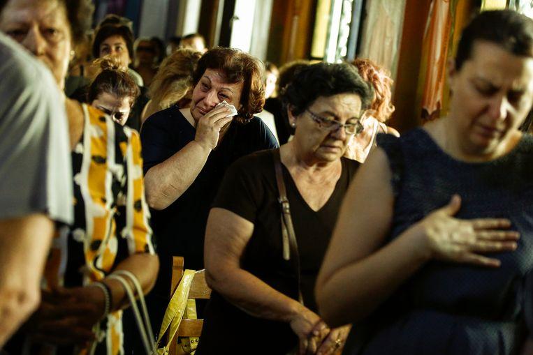 Rouwenden bij een herdenkingsdienst voor de slachtoffers van de bosbranden, in de Grieks orthodoxe kerk van Mati. Beeld EPA