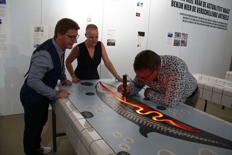 Emanuel Demey en Geert Werkers die de expo vormgaf samen met gedeputeerde Jurgen Vanlerberghe die een spel uittest