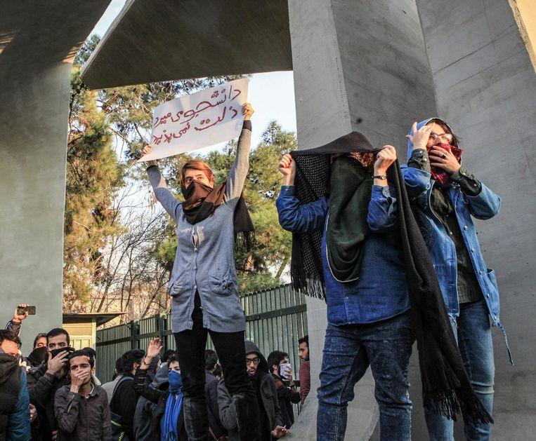 Demonstranten tegen het beleid van de Iraanse regering proberen zich te beschermen tegen traangas bij de universiteit van Teheran. Beeld null