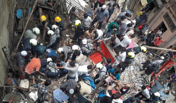 Reddingswerkers en omwonenden zoeken naar overlevenden onder het puin.