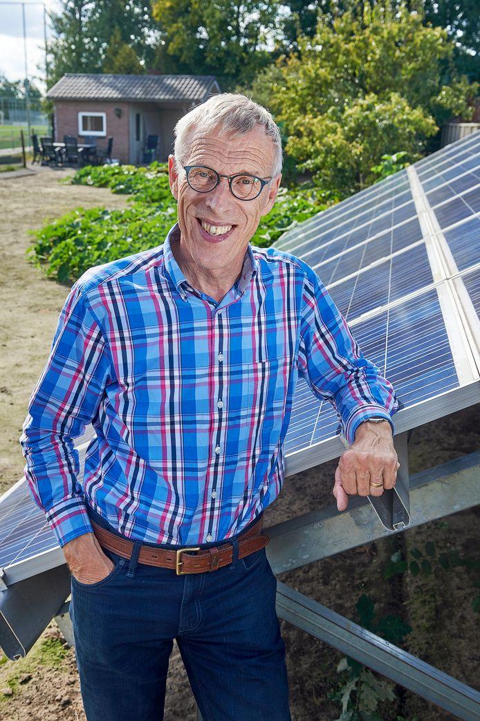 Adrie Geerts bij de zonnepanelen in zijn moestuin.