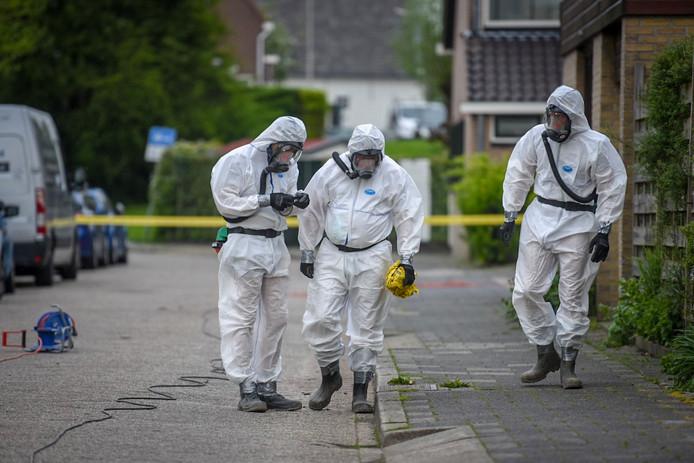 Speciaal geklede asbestsaneerders werden ingeschakeld om asbest op te ruimen dat door stevige wind in een woonwijkwas beland na een brand bij boer William Jacobs uit  Hazerswoude-Dorp. (Archieffoto).