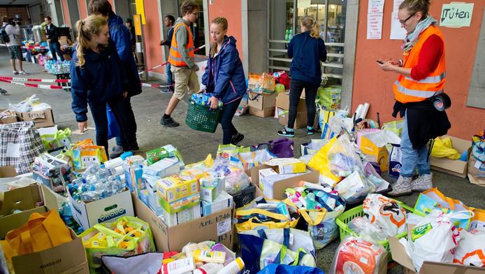 De vluchtelingen worden op het station in München onthaald met drinken, eten en speelgoed.