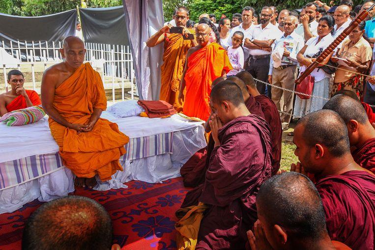 De boeddhistische monnik Athuraliye Rathana (l) ging zaterdag in hongerstaking om het aftreden van islamitische politici af te dwingen. Beeld EPA