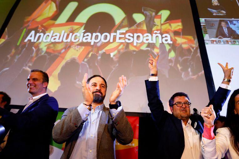 VOX-leider Santiago Abascal (midden) en regionale kandidaat Francisco Serrano (rechts) vieren feest na hun groei van 0 naar 12 zetels in regionale verkiezingen in Andalusië.  Beeld REUTERS