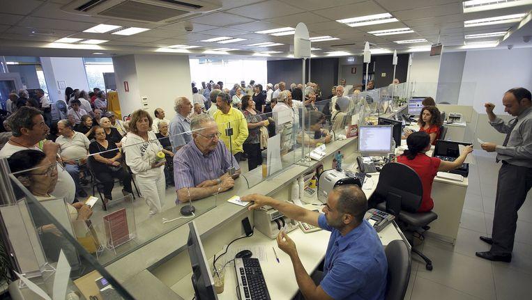 Pensioengerechtigden komen geld halen in een vestiging van Piraeus Bank op Kreta. De banken werden drie weken gesloten gehouden om een bankrun te voorkomen. Beeld null