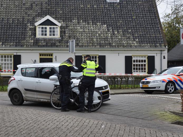 Politie houdt de fiets tegen de auto aan, op de plek van de botsing.