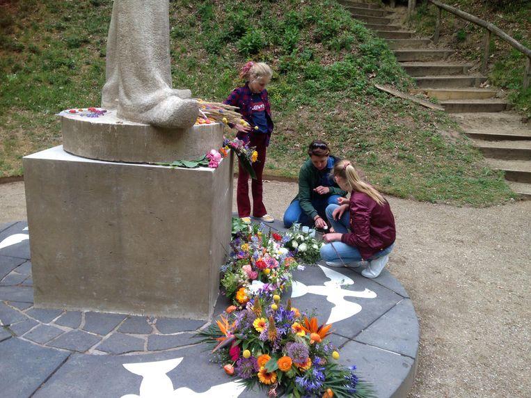 De twee nichtjes steken een kaarsje aan. Het achterste meisje is de jeugdburgemeester van Leusden, zonder Corona zou zij daar geweest zijn tijdens de officiële dodenherdenking op 4 mei. Dit was een mooie gelegenheid om een bijdrage te doen aan het in stand houden van een meer dan ooit waardevolle traditie. Beeld Evert van Ginkel