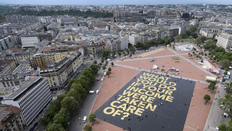'Wat zou je doen als je van een vast inkomen was verzekerd?'. Deze vraag stond op een grote poster die half mei op een plein in Genève werd uitgerold. De poster kreeg vanwege de afmetingen ook een vermelding in het Guinness Book of Records. Beeld afp