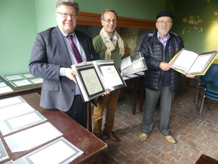 Burgemeester Koenraad Degroote, Denis Haerens en Jules Desmet tonen enkele rouwbrieven.