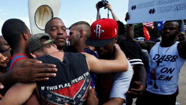 Mensen biddend in een groepsomhelzing na een Black Lives Matter-protest na 'Dallas'. Beeld REUTERS