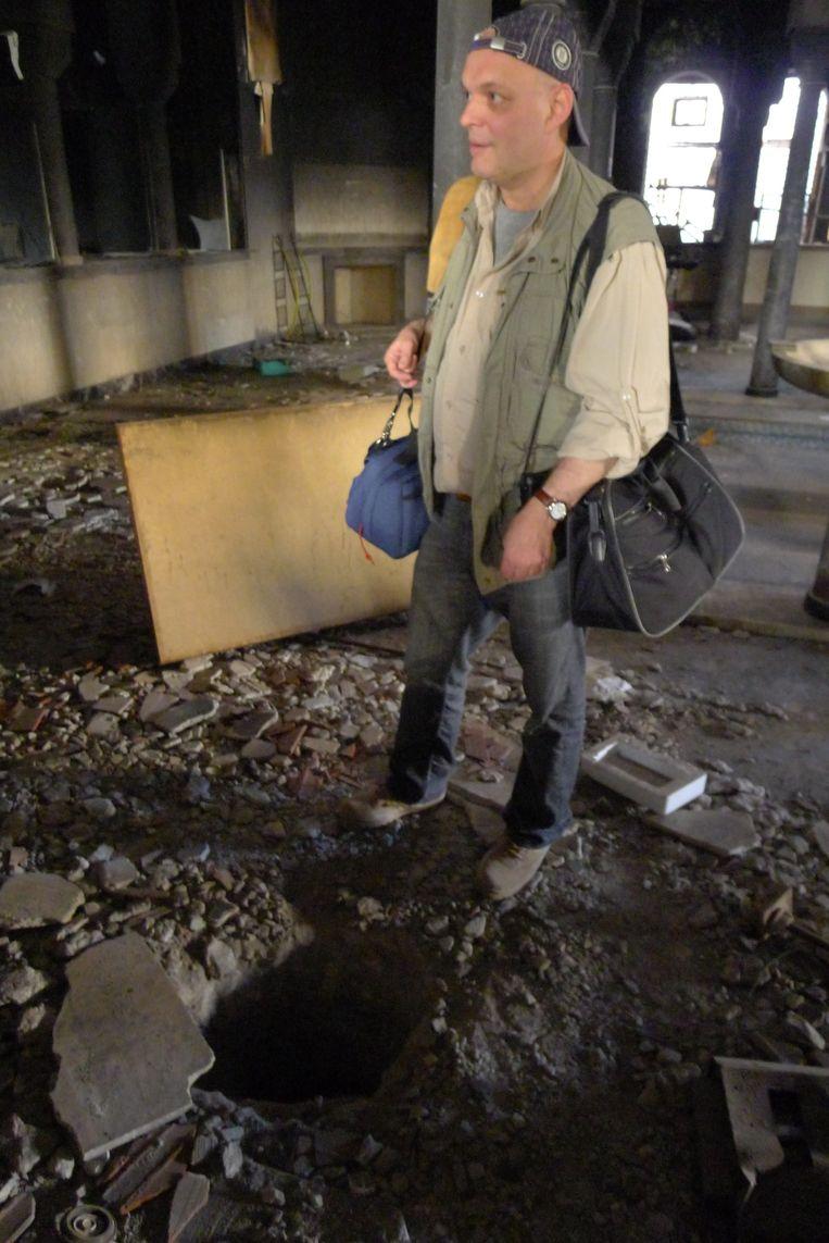 Kila in een verwoeste bank in de Libische stad Benghazi, waar een gouden schatkist was gestolen via een gat in de grond. Beeld Joris Kila