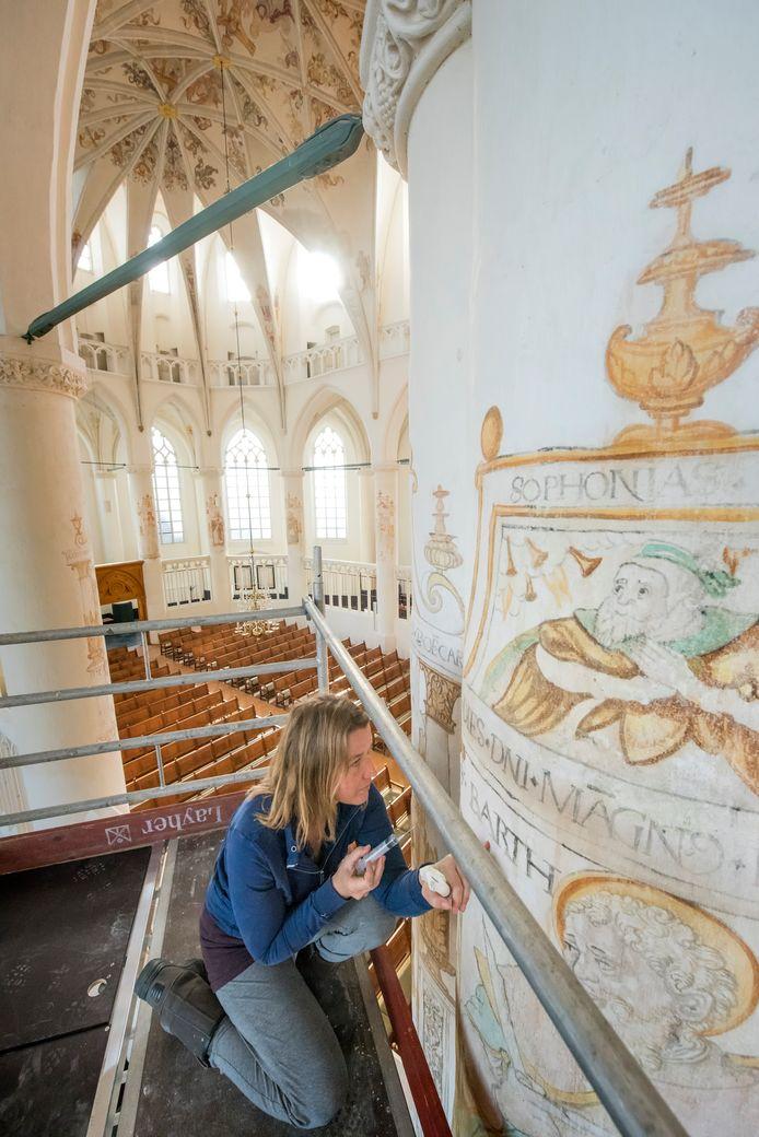 Restaurator Aafje Bouwhuis van Bouwhuis en Journée restaureert schilderingen in de Grote Kerk in Harderwijk.