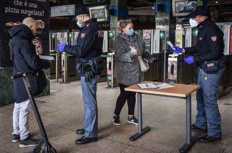 Italiaanse agenten met maskers controleren reizigers op het Cadorna-station in Milaan. Beeld EPA