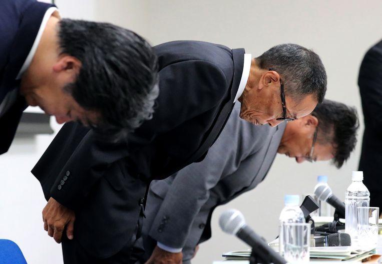 Yasuhiro Yamauchi, de chief competitive officer van Nissan, buigt naar de aanwezigen tijdens de persconferentie op het hoofdkantoor van het bedrijf in Yokohama, waar de fraude werd erkend. Beeld EPA