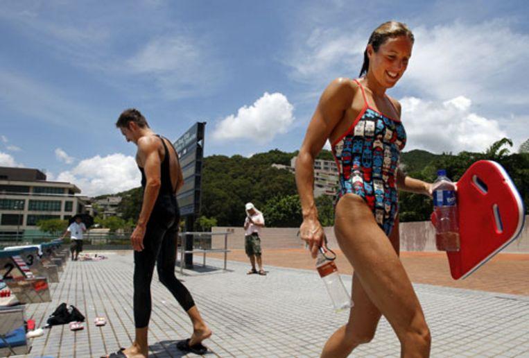 Marleen Veldhuis en Pieter van den Hoogenband verlaten het zwembad in het Chinese Hongkong na afloop van de training. (ANP) Beeld null