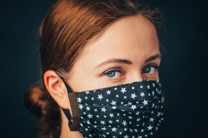 Foto ter illustratie. Een vrouw draagt een modieus mondkapje.