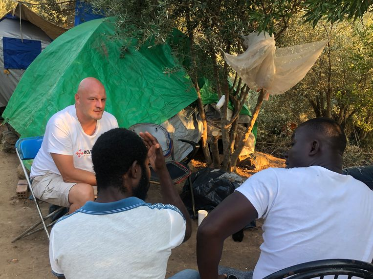 Vrijwilliger Martijn van Ommen in gesprek met een groep Ghanezen die hem helpen bij het opruimen van afval. Beeld Thijs Kettenis